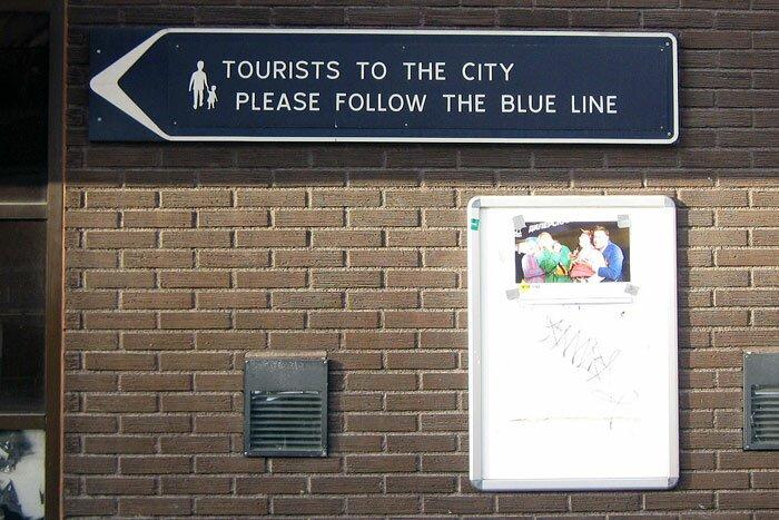 Табличка: Tourists to the city please follow the blue line